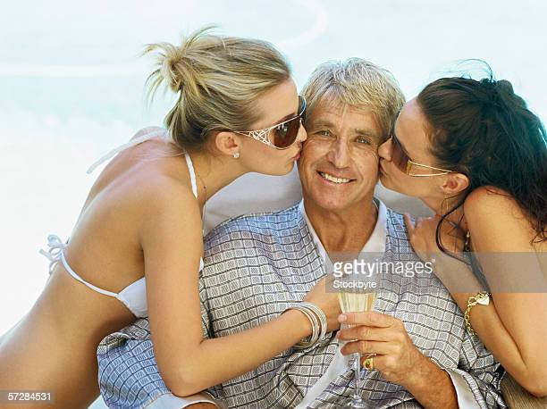 Two young women kissing a mid adult man