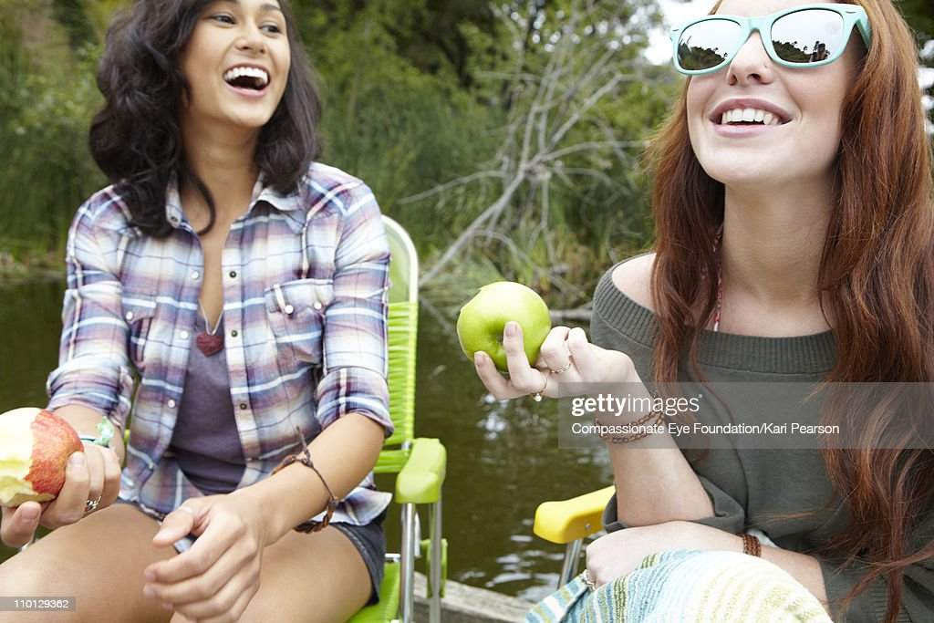 Two young women laughing and eating apples : Stock Photo