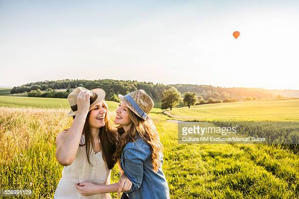 Two young women, laughing and fooling around in field