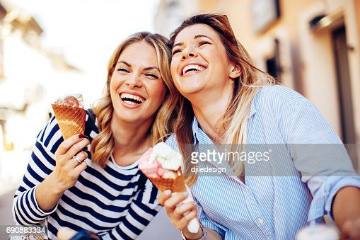 Two young women laughing and holding ice cream in hand : Stock Photo