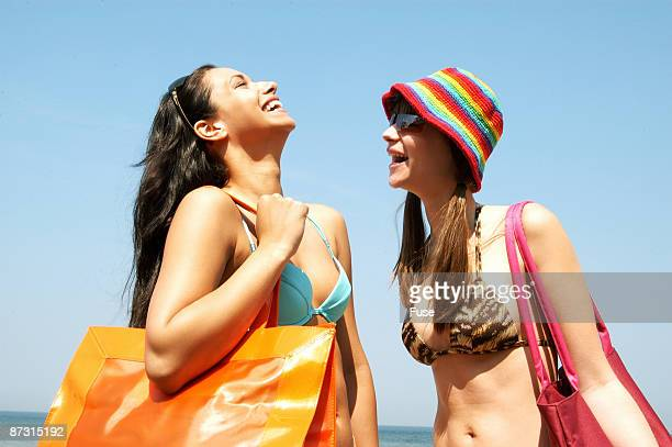 Two young women laughing on the beach
