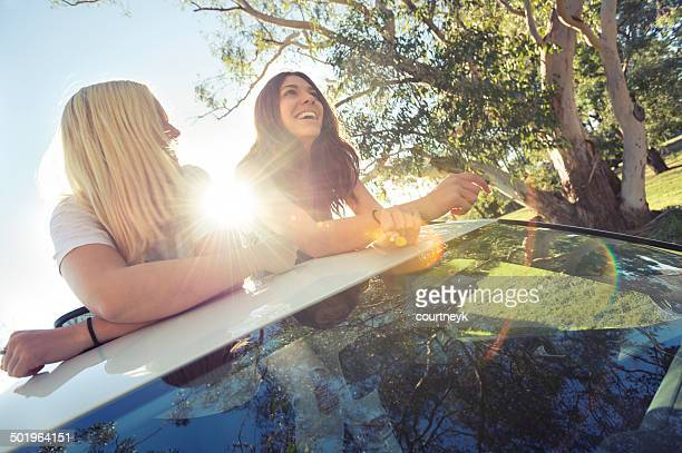 two young women leaning out of a sunroof backlight by the sun