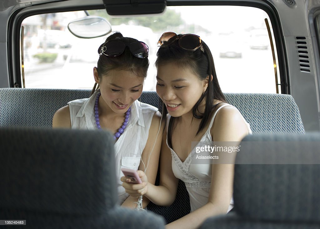 Two young women listening to MP3 player in a car : Stock Photo