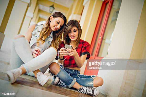 Two young women listening to music by smart phone