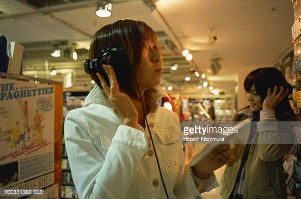 Two young women listening to music in record shop