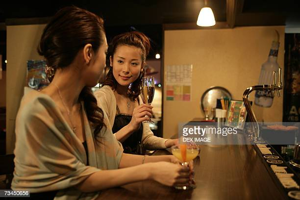 Two young women looking at each other at a bar counter in a nightclub