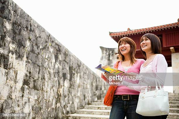 Two young women looking at guidebook while sightseeing, smiling