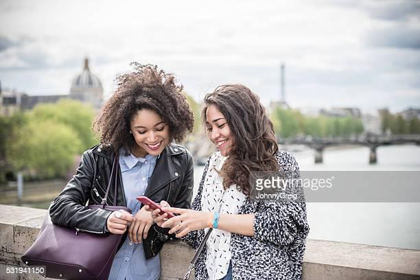 Zwei junge Frauen schaut an Mobiltelefon wirst