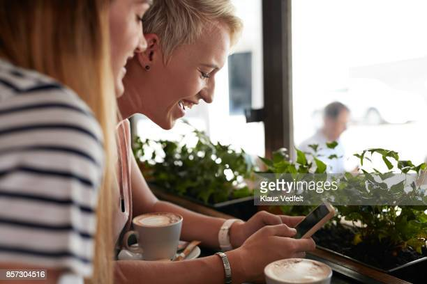 Two young women looking at phone together, at café