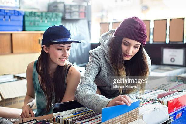 Two young women looking at records in store