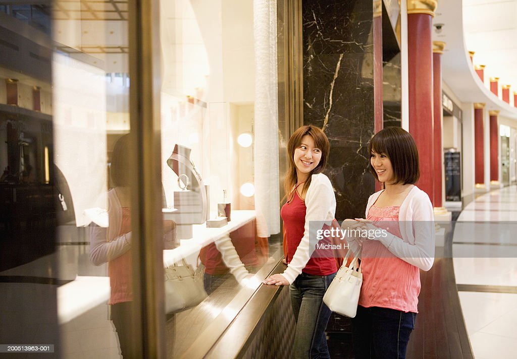 Two young women looking at window display in retail store, smiling : Stock Photo