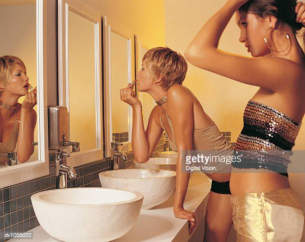 Two Young Women Looking in the Mirror in a Nightclub Toilet
