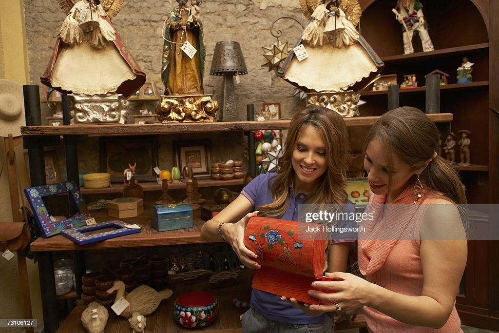 Two young women looking inside an antique box and smiling