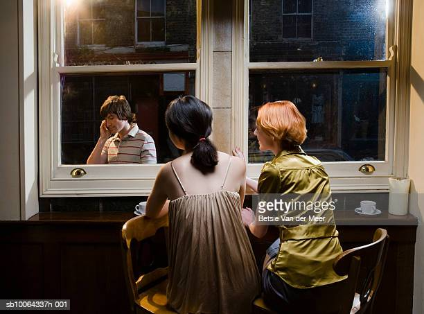 Two young women looking through window at man using mobile phone