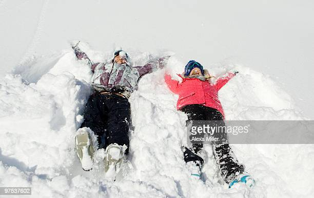 Two young women making snow angels.