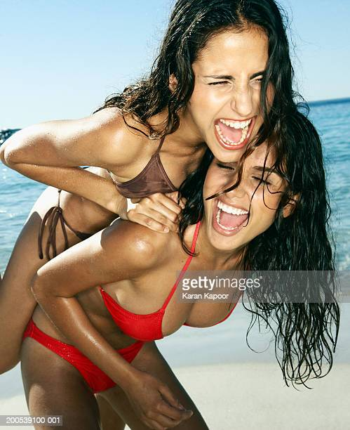 Two young women messing about on beach, laughing