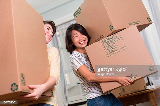 Two young women moving boxes