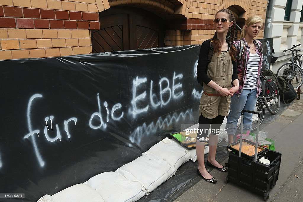 Two young women offer cake and coffee to volunteers stacking sandbags against rising floodwaters in the residential Werder district of the city center next to the swollen Elbe river on June 9, 2013 in Magdeburg, Germany. Magdeburg is enduring its highest floodwaters in its 1,200 year history and local authorities have called on 23,000 residents from outlying areas to evacuate their homes. Catastrophic flooding has hit portions of southern and eastern Germany that has left at least seven people dead and forced tens of thousands to flee their homes. Towns in northern Germany downstream from the Elbe are also bracing for floods in coming days.