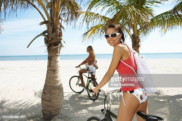 Two young women on bicycles on beach, portrait (focus on foreground)