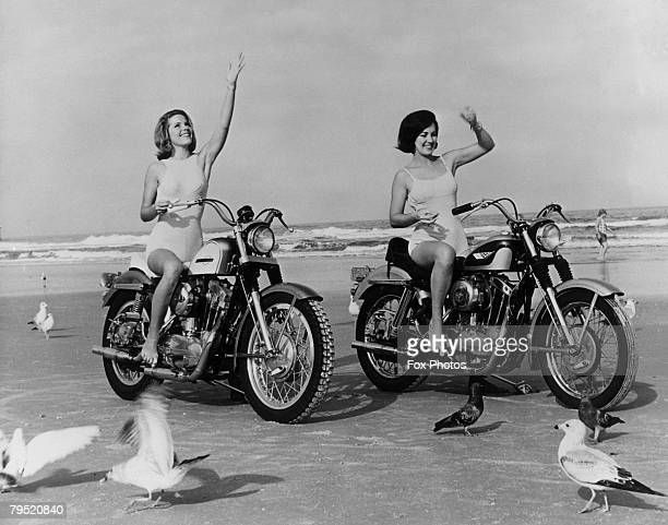 Two young women on motorcycles feed the seagulls on the beach at Daytona Florida 10th October 1968
