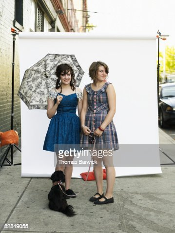 Two young women on sidewalk with dog
