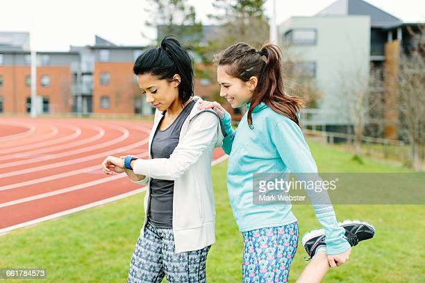 Two young women outdoors, exercising, stretching