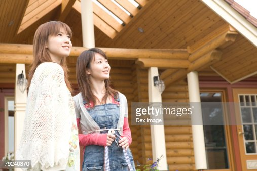 Two young women outside a cabin : Stock Photo