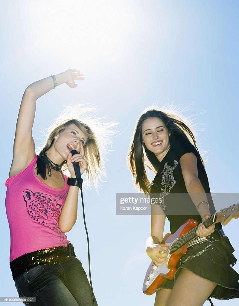Two young women playing guitar and singing outdoors : Stock Photo