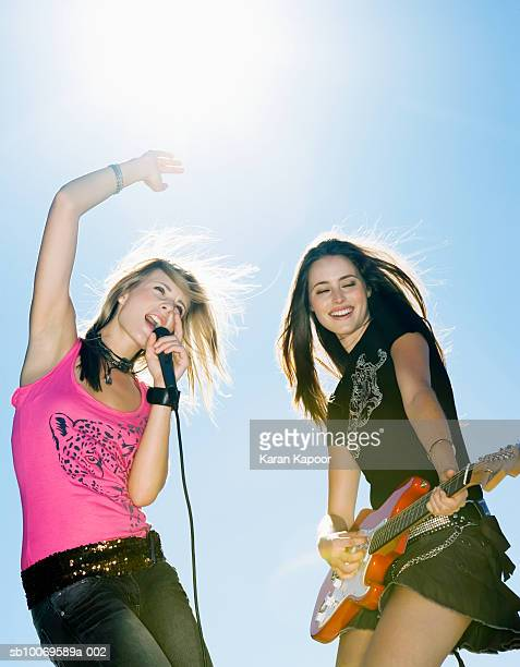 Two young women playing guitar and singing outdoors