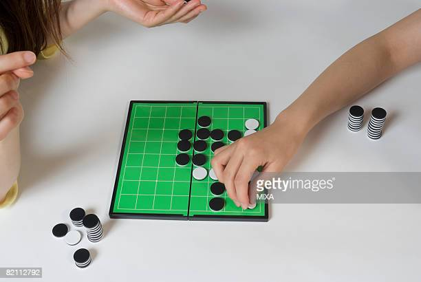 Two young women playing Othello game