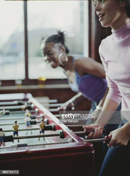 Two young women playing table football