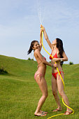 Two young women playing with hose in backyard