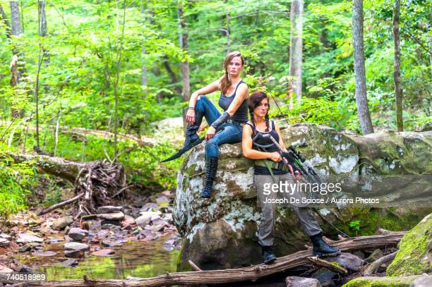 Two young women posing in forest with their hunting gear