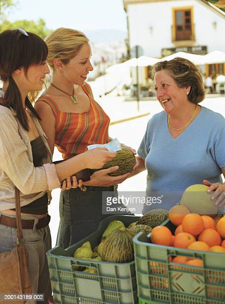 Two young women purchasing fruit from street vendor