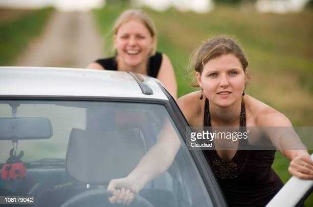 Deux jeunes femmes pousser voiture sur la route