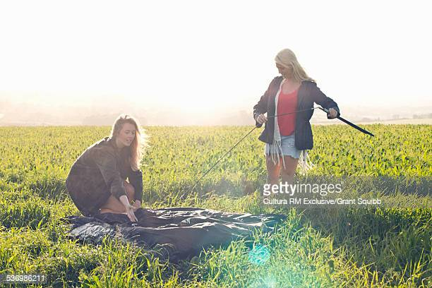 Two young women putting up tent in grassy field, Dorset, England