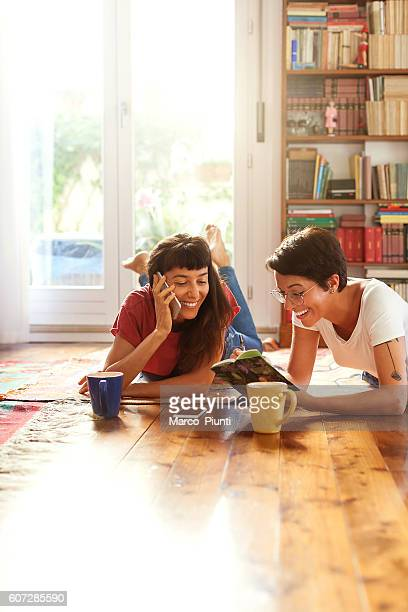 Two young women relaxing at home enjoying free time