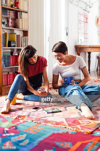 Two young women relaxing at home enjoying free time