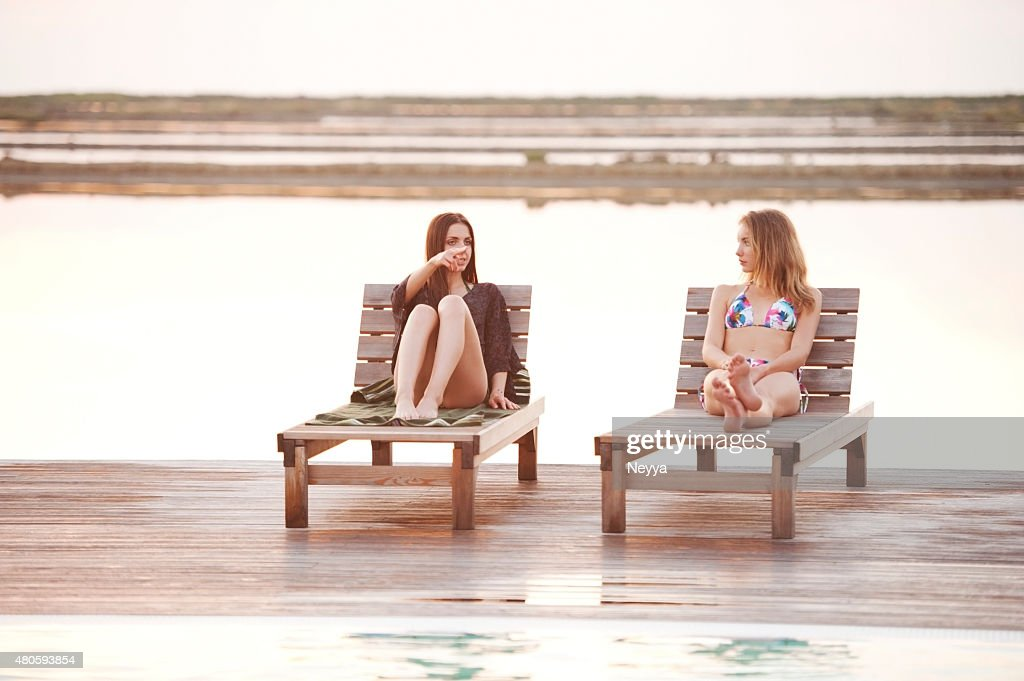 Two Young Women relaxing at the Swimming Pool : Stock Photo