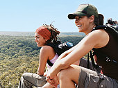 Two Young Women Relaxing From Hiking and Looking at the View Over Treetops