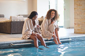 Two young women relaxing on edge of spa swimming pool
