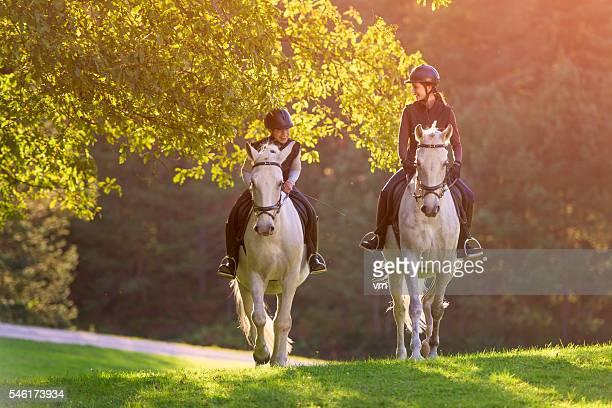 Deux jeunes femmes équitation dans la nature