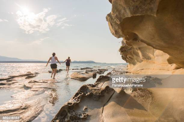 Two Young Women Running Along Ocean Beach of Sandstone Formations