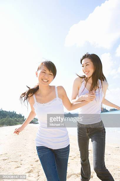 Two young women running on beach, laughing