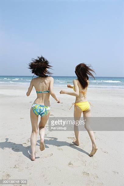 Two young women running on beach, rear view