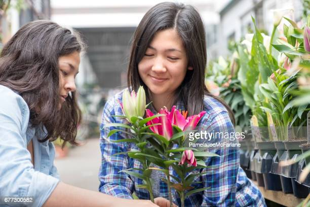 Two Young Women Shopping for Potted Flower Plant at Nursery