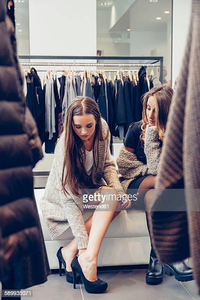 Two young women shopping for shoes in a boutique