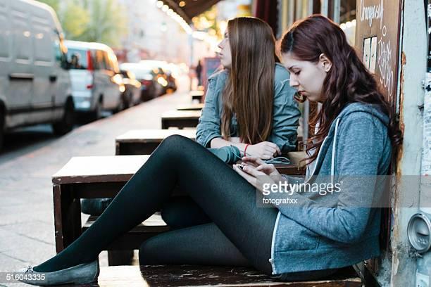 Zwei junge Frauen Sitzen im Straßencafé Kreuzberg in Berlin.