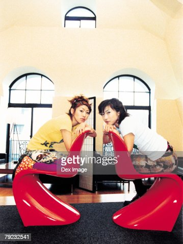 Two young women sitting across from each other : Stock Photo