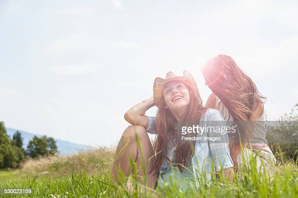 Two young women sitting chatting in grassy field